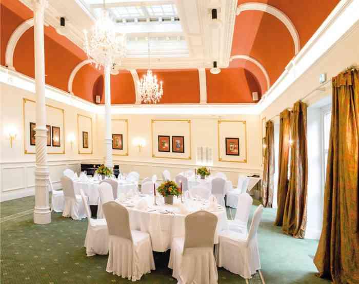 Der Jugendstilsaal im Palais Esplanade mit roter Decke und Oberlicht aus buntem Glas.