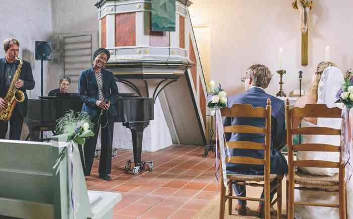 Sängerin singt für ein Brautpaar während der Trauung in der Kirche