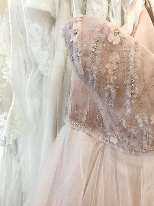 Die Kombination von gerafften Tüll-Applikationen mit Strass, Perlen, Herzen und Blumen verleihen diesem Kleid in gedecktem zarten Rose den zauberhaft märchenhaften Look.