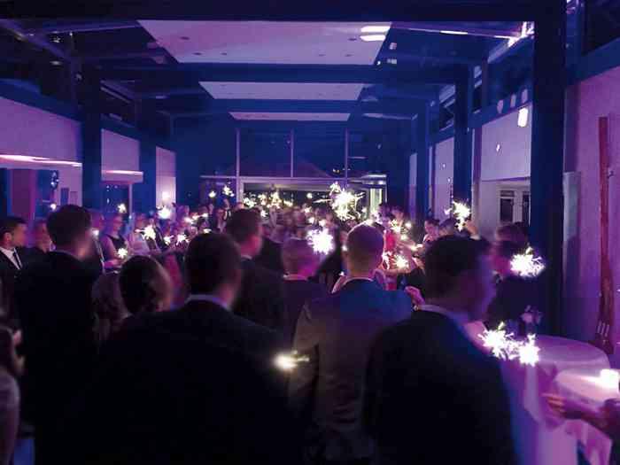 Hochzeitsgäste und Wunderkerzen im Foyer der Hochzeitslocation der Alsterköche im Ruder-Club Favorite Hammonia.