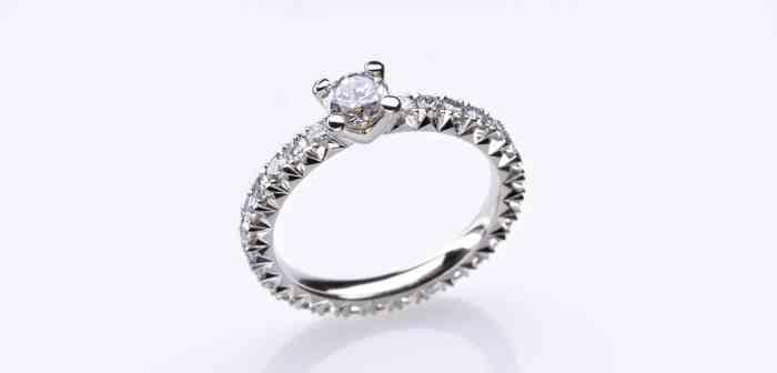 Verlobungsring mit einem großen Diamanten in der Mitte und kleinen Brillanten als Rahmen.