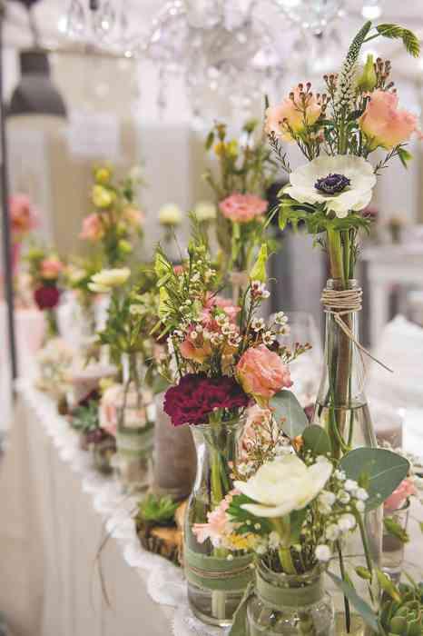 Auf der Hochzeitsmesse Hochzeitstage Hamburg in Halle B7 werden Brautpaaren Tischdekorationen mit Wiesenblumen gezeigt.
