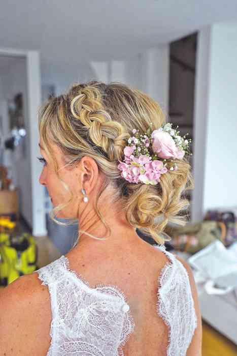 Brautfrisur geflochten und mit eingstecketen Blumen Die Brautzauberin