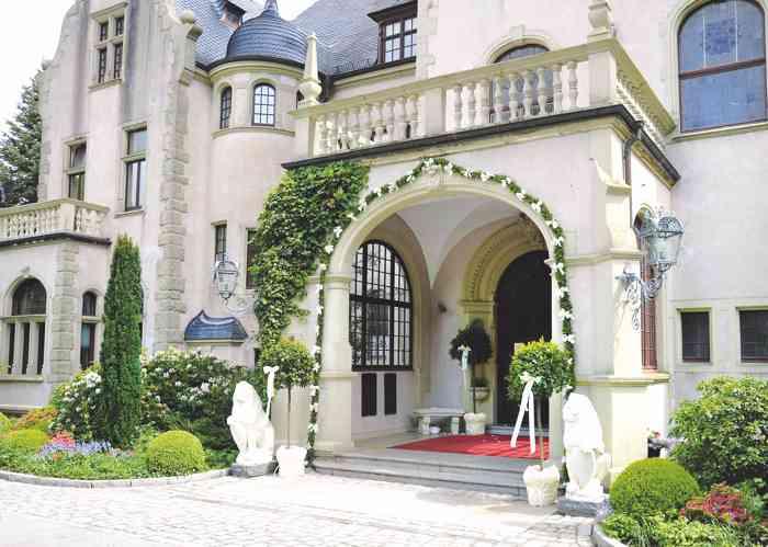 Eingangsportal Schloss Tremsbüttel mit grünweißer Girlande geschmückt.