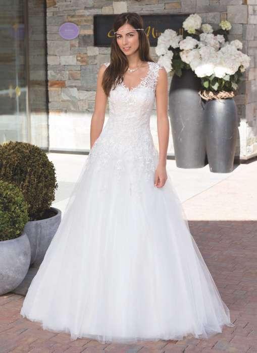 Das Brautkleid Zelda von Kleemeier hat einen weiten Tüllrock und florale Spitze in den Trägen, die sich fließend in der Korsage fortsetzen.
