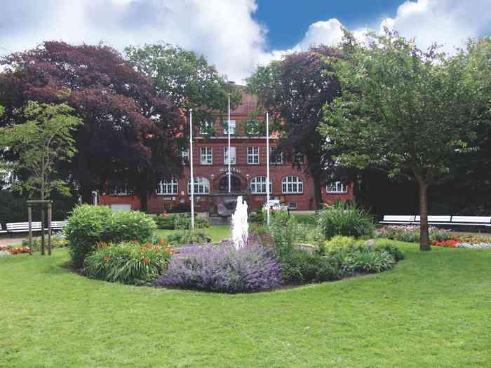 Rathaus Büsum mit Gartenanlagen im Vordergrund.