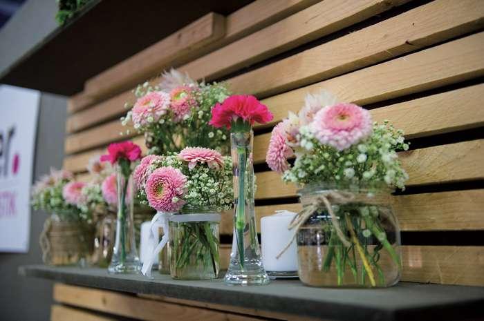 Auf der TrauDich! Hochzeitsmesse im Terminal Tango Hamburg zeigen die Aussteller Blumendekorationen mir rosa Belleys.