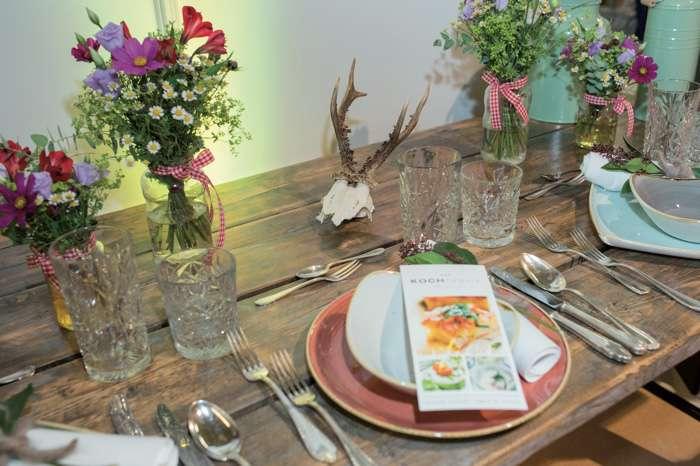 Auf der TrauDich! Hochzeitsmesse im Terminal Tango Hamburg zeigen die Aussteller Tischdekorationen mit Wiesenblumensträußen.