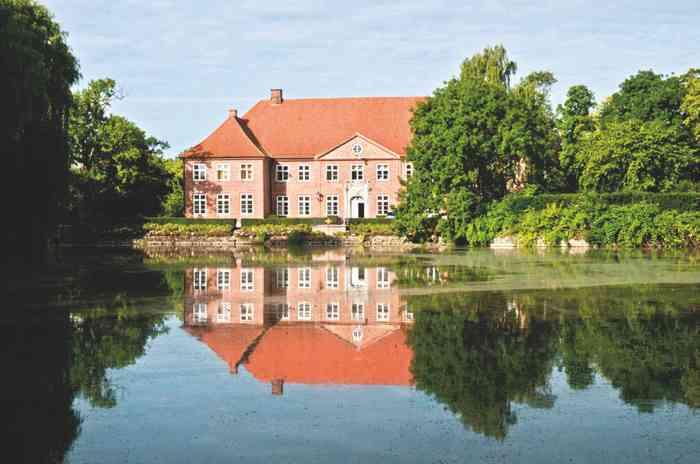 Hochzeitslocation Herrenhaus Borghorst mit Gebäude und See.