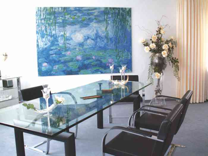 Trauraum des Standesamtes Meine im Rathauses Samtgemeinde Papenteich. Der Trautisch aus Glas steht vor einem Druck von Monets Seerosenbild. Die Lederstühle sind modern.