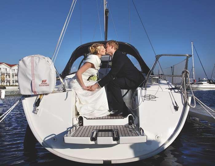 Brautpaar küsst sich auf Segelboot. Marina Iberhotel Boltenhagen.
