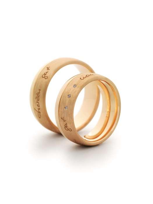 Trauringe aus Gelbgold mit drei kleinen Brillanten im Damenring und einer handschriftlichen Gravur in beiden Ringen aus der Goldschmiede Dallmann.