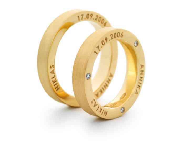 Trauringe aus Gelbgold mit drei Brillanten in der Seitenfläche des Damenrings und den Namen der Eheleute ebenfalls in der Seite der Ringe aus der Goldschmiede Dallmann.