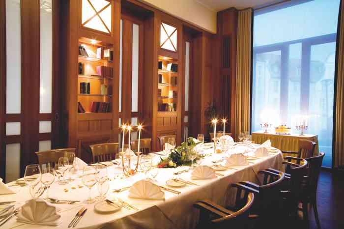 Festraum mit eingedeckten Tisch und brennenden Kerzen der Hochzeitslocation Steigenberger Hotel Sonne in Rostock.