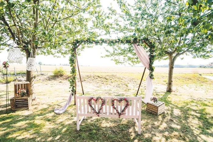 Trauung unter freiem Himmel auf grüner Wiese weiße Bank mit Blumenherzen Traubogen Blumengirlande