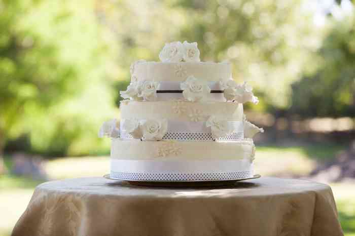 Mehrstöckige weiße Hochzeitstorte auf Tisch