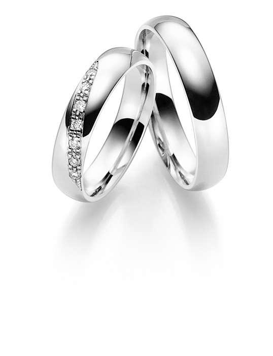 Trauringe aus glänzendem Weißgold mit Diamanten.