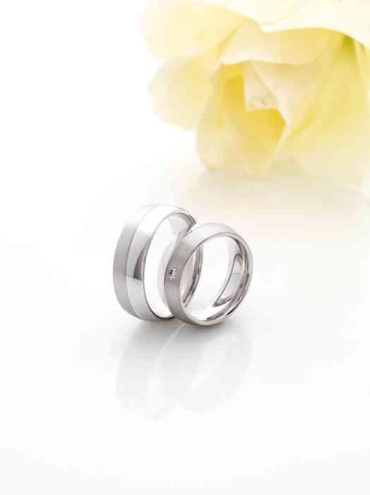 Trauringe aus zwei verschiedenen Edelmetallen mit einem kleinen Brillanten für die Braut.