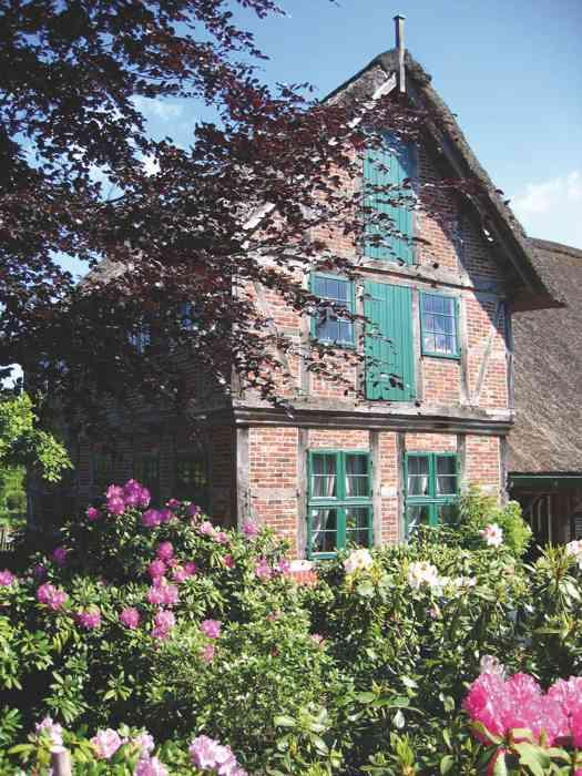 Eingangsgebäude des Freilichtmuseums am Kiekeberg mit blühenden Rhododedonbüschen.