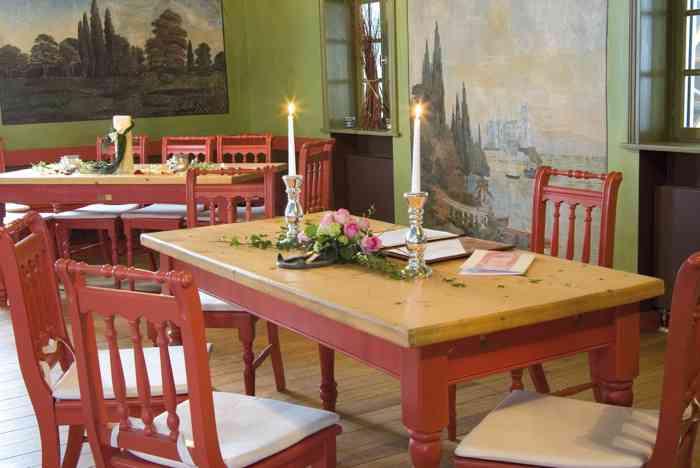 Trautisch mit Kerzen im Tanzsaal in der Hochzeitslocation Brennerei auf dem Gelände des Freilichtmuseums am Kiekeberg.