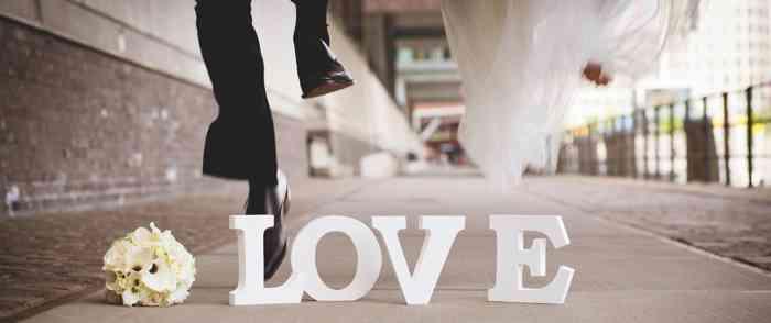 Hochzeitspaar springt über den Schriftzug LOVE.