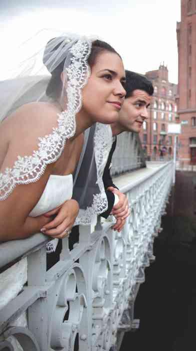 Hochzeitspaar schaut von einer Brücke an das Geländer gelehnt. Hochzeitsfoto in der Hamburger Speicherstadt.
