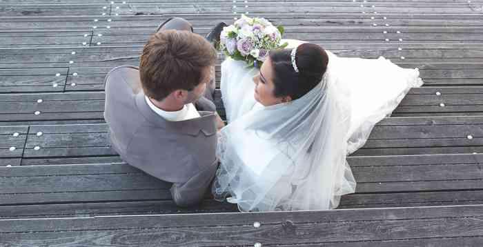 Hochzeitspaar sitzt auf einer Treppe. Hochzeitsfoto in der Hamburger Speicherstadt.