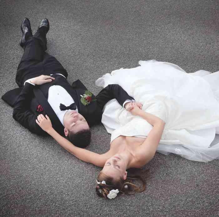 Hochzeitspaar liebt auf dem Boden und umarmt sich. Hochzeitsfoto in der Hamburger Speicherstadt.