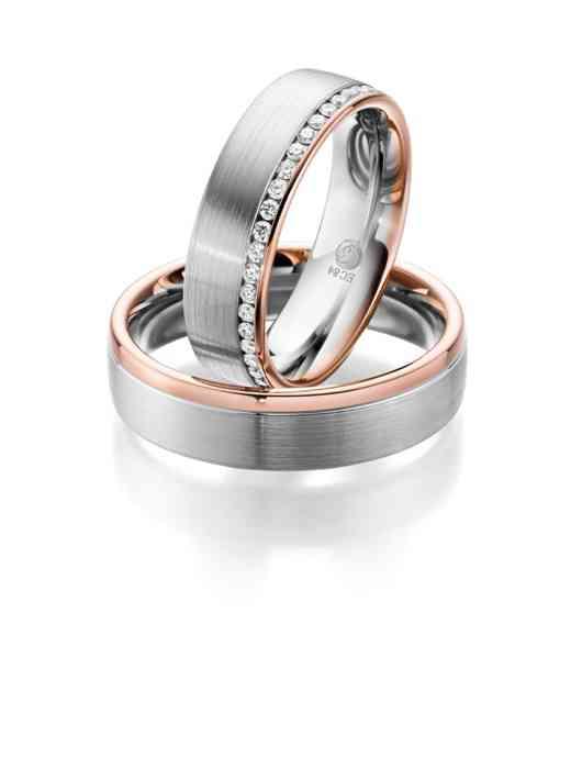 Breite Trauringe mit einem Rosegold-Akzent. Der Ring der Braut ist mit kleinen Diamanten versetzt.