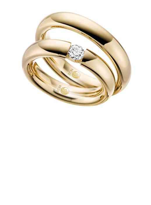 Trauringe Gelbgold. Der Trauring der Braut ist mit einem großen Diamanten besetzt.