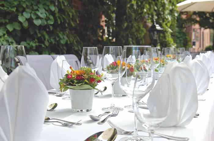 Weiß eingedeckter Tisch im Garten der Hochzeitslocation Antikhof Bissee.