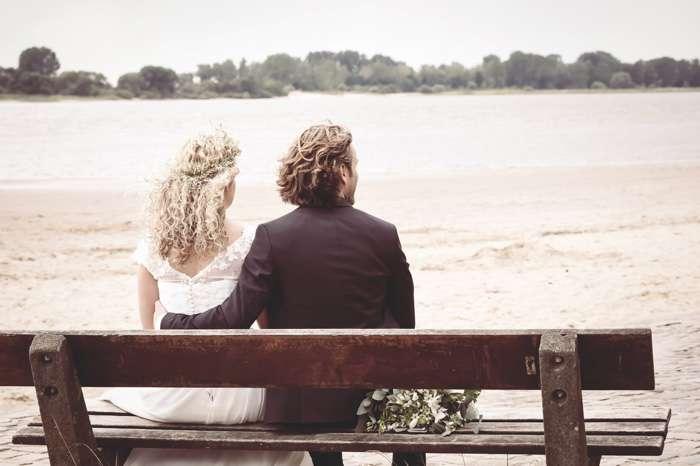 Die Hochzeitsfotografin Mascha Pohl - map - aus Hamburg zeigt auf diesem romantischen Hochzeitsfoto ein Brautpaar auf einer Bank an der Elbe bei Hamburg.