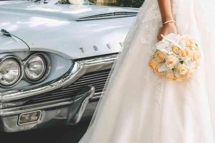 Die Hochzeitsfotografin Mascha Pohl - map - aus Hamburg zeigt auf diesem romantischen Hochzeitsfoto eine Braut mit Brautstrauß aus Rosen vor einem Oldtimer Hochzeitsfahrzeug Ford Thunderbird in hellblau.