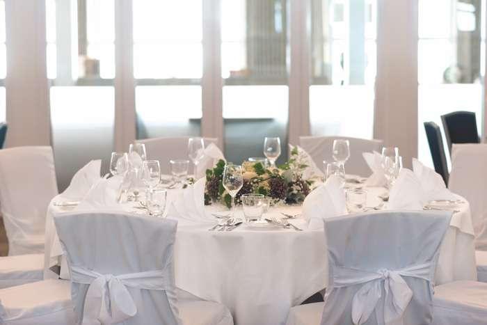Festsaal mit schön gedecktem Tisch der Hochzeitslocation Das Neue Schulauer Fährhaus an der Elbe.