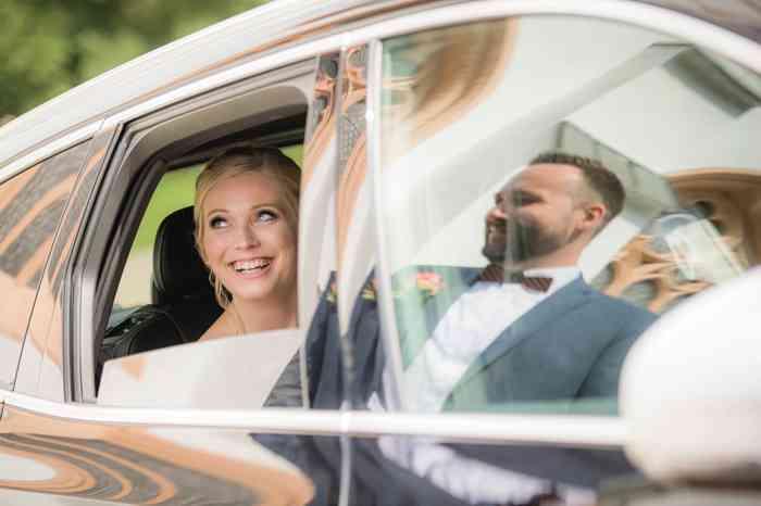 Strahlendes Brautpaar im Hochzeitsauto