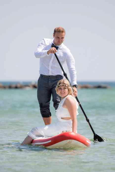 Strandhochzeit auf Fehmarn Brautpaar beim Stand-Up Paddling