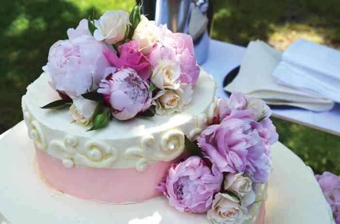 Hochzeitstorte in Rose mit Rosen und Bauernrosen dekoriert der Hochzeitslocation Kurhaus am Inselsee in Güstrow Mecklenburg-Vorpommern.