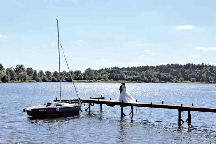Der Inselsee mit Brautpaar auf einem Steg mit Segelboot im Wasser.