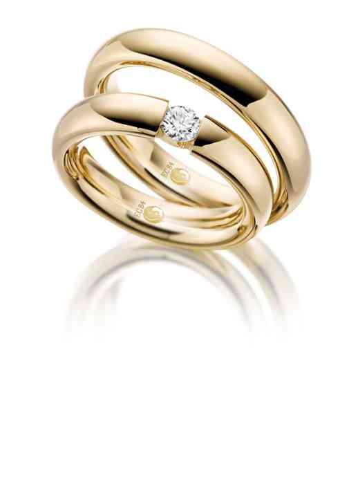Trauringe aus Gelbgold. Der Ring der Braut ist durch einen großen Diamanten veredelt.