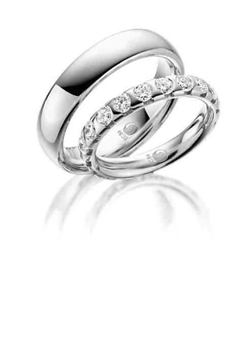 Trauringe aus Weißgold, glänzend, mit mehreren Diamanten für die Braut.