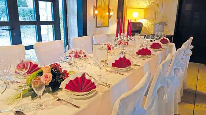 Festlich eingedeckte Tische für Brautpaar und Gäste.