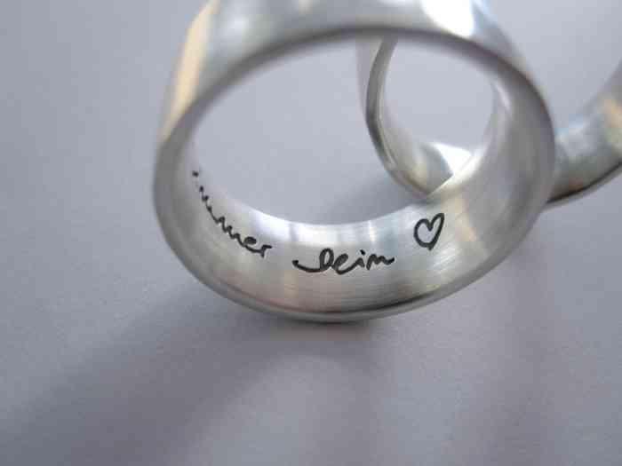 Handschriftliche Gravur in den Verlobungsringen und Trauringen von liebes Stück mit persönlichen Worten oder dem Namen des Partners.