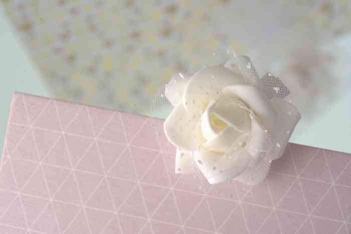 Eine weiße Rose an einer rosa Glückwunschkarte der Papeterie und Schreibwaren Otto F.K. Koch.