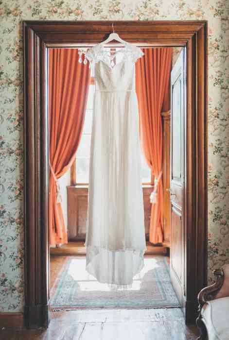 Brautkleid hängt im Türrahmen bei Gegenlicht.