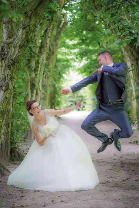 Brautpaar springt vor Freude in die Luft.