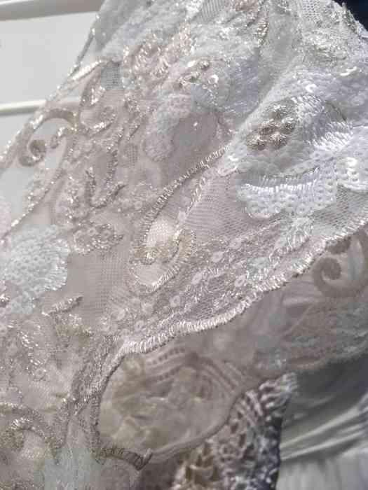 Wediva zeigt ein elegantes Brautkleid mit silbernen Spitzen