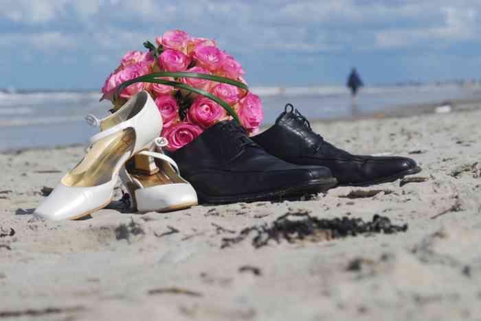 Brautschuhe mit Blumenstrauss am Strand.