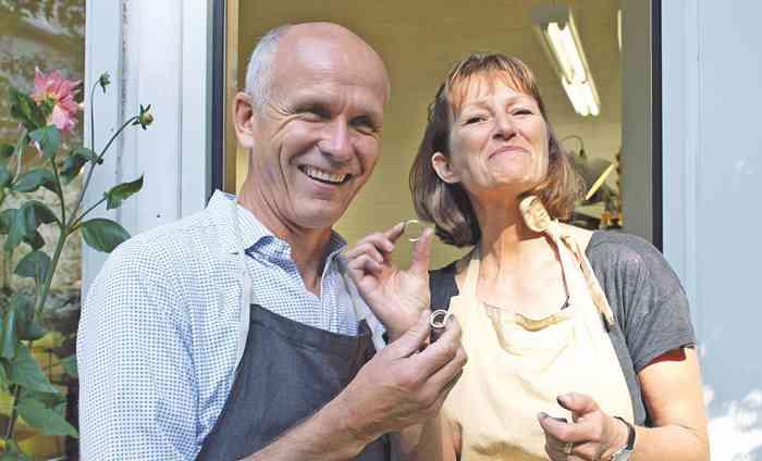 Glückliches älteres Paar freut sich über selbst geschmiedete Trauringe