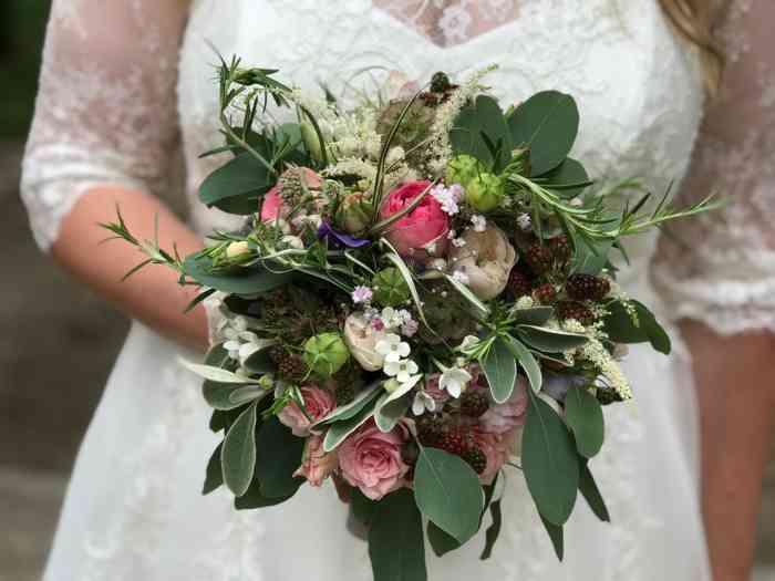 Verspielter Brautstrauß mit rosa Rosen, Brombeeren, Thymian und weiteren Kräutern.