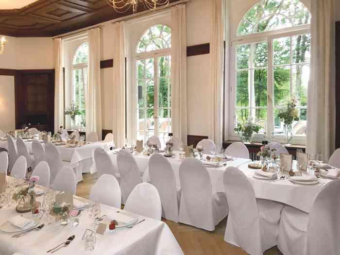 Hochzeitslocation Haus Schnede Festsaal mit eingedeckten Tischen.